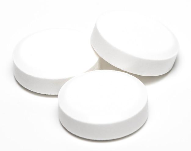 Pilule blanche isolée sur gros plan fond blanc.