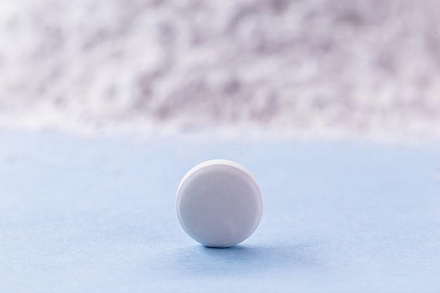 Pilule blanche avec de l'oxyde de zinc en arrière-plan, concept de vitamine.