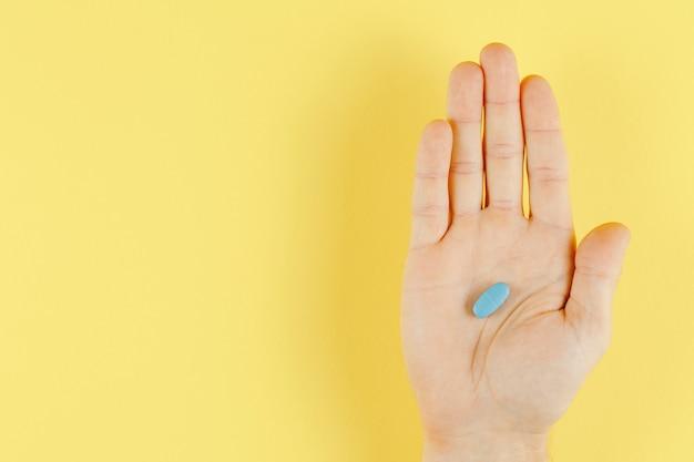Pilule bleue à la main sur la vue de dessus du mur jaune, mise à plat et beaucoup d'espace libre, mur médical
