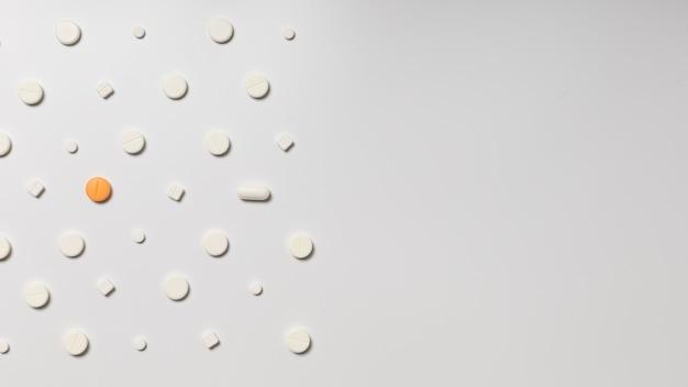 Une pilule de couleur sur fond de pilules blanches