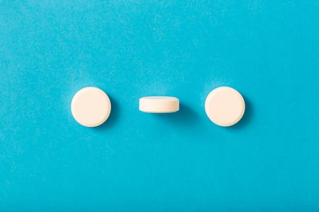 Pilule debout entre les deux comprimés blancs sur fond bleu