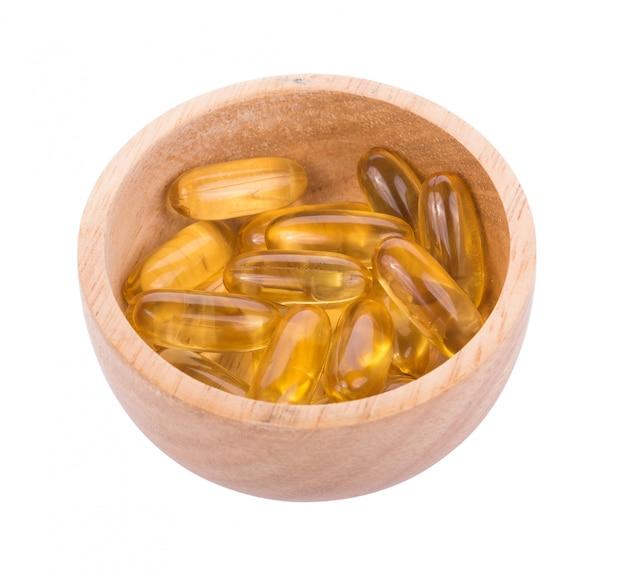 Pilule d'huile de poisson dans un bol en bois sur mur blanc
