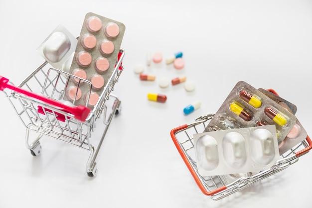 Pilules et ampoules de médicaments à l'intérieur des deux paniers d'achat sur fond blanc