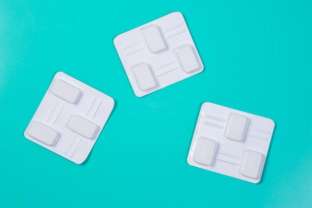 Pilules antibactériennes vaginales blanches sur surface bleue