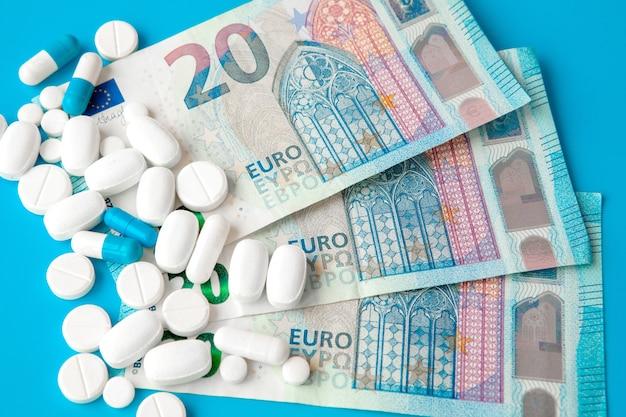 Pilules sur l'argent de l'euro sur bleu.