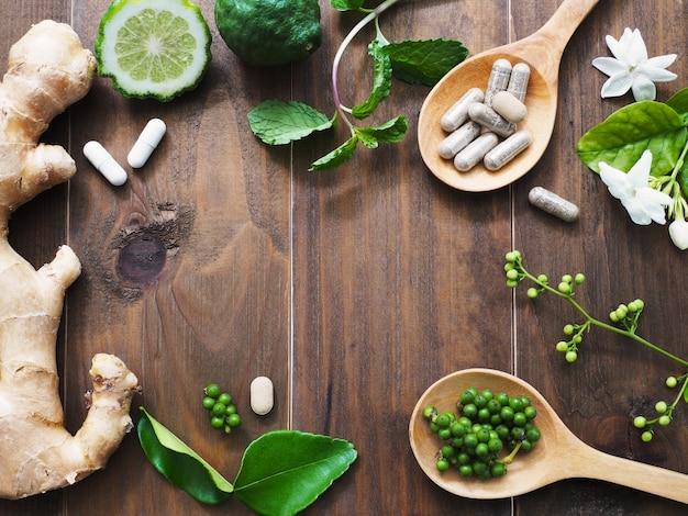 Pilules à base de plantes dans la cuillère en bois et les herbes