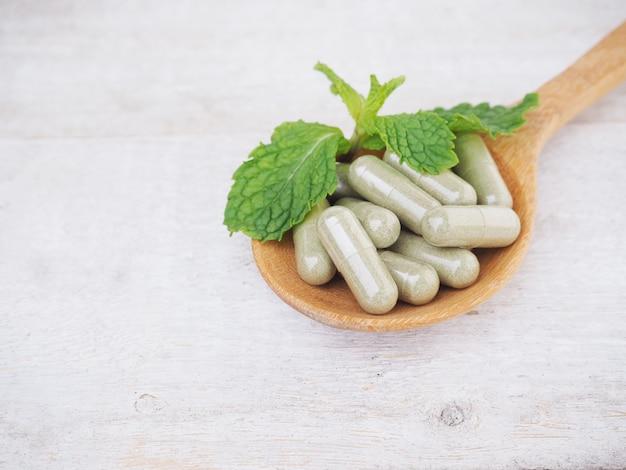 Pilules à base de plantes et feuilles de menthe sur cuillère en bois