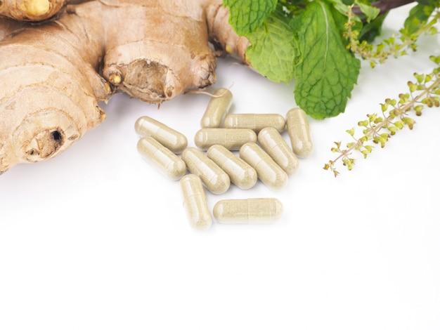 Pilules à base de plantes avec racine de gingembre et plante verte