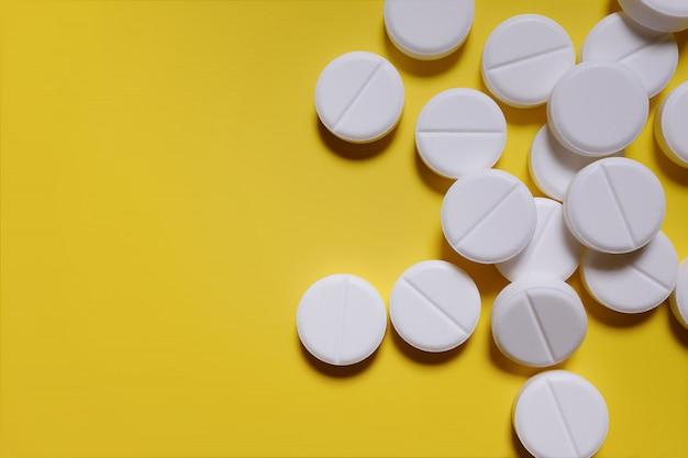 Pilules blanches, analgésiques sur fond jaune.