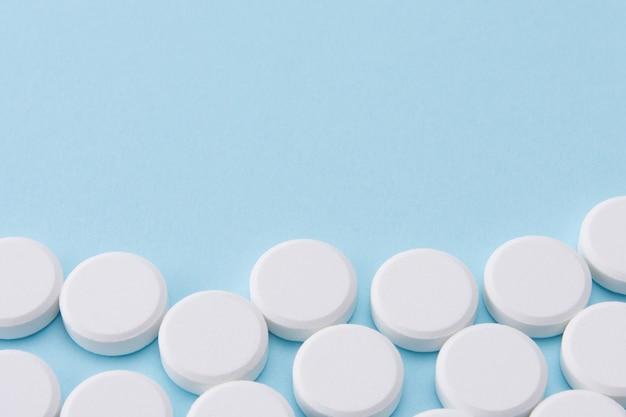 Pilules blanches sur bleu