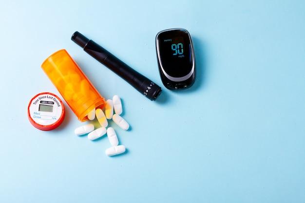 Pilules blanches dans une bouteille médicale orange avec lecteur de glycémie sur fond bleu avec espace de copie