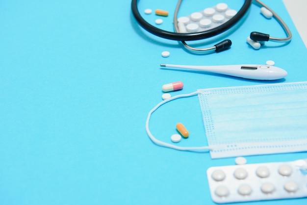 Pilules blanches éparpillées sur table bleue.concept médical, pharmacie et soins de santé. pilules blanches de fond bleu avec un statoscope médical, vue de dessus.