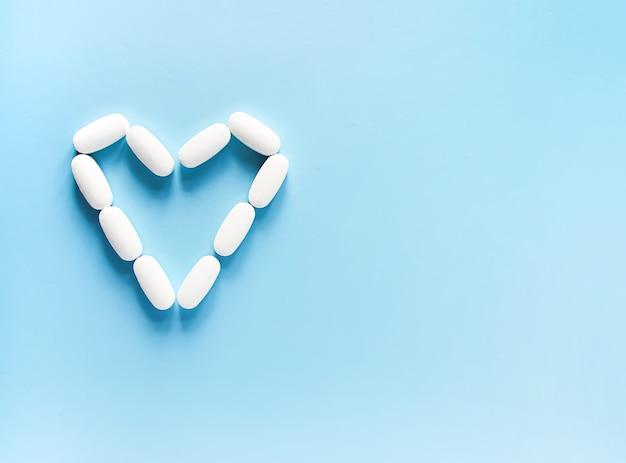 Pilules blanches en forme de coeur.