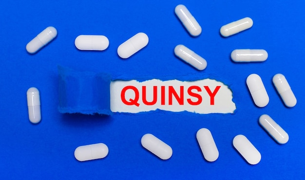 Les pilules blanches reposent sur une belle surface bleue. au centre se trouve du papier blanc avec l'inscription quinsy