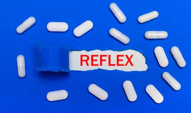 Les pilules blanches reposent sur une belle surface bleue