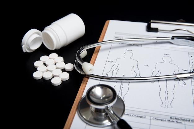 Pilules blanches et un stéthoscope de bouteille et une fiche médicale sur un fond noir.