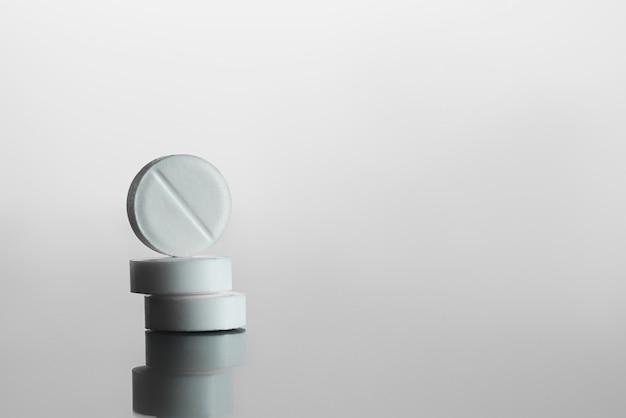 Pilules blanches sur la surface du miroir, gris bg