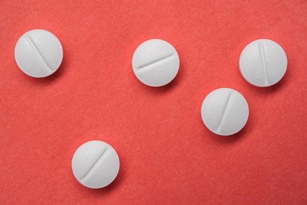 Pilules blanches sur une surface rouge