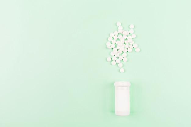 Pilules blanches sur table verte.