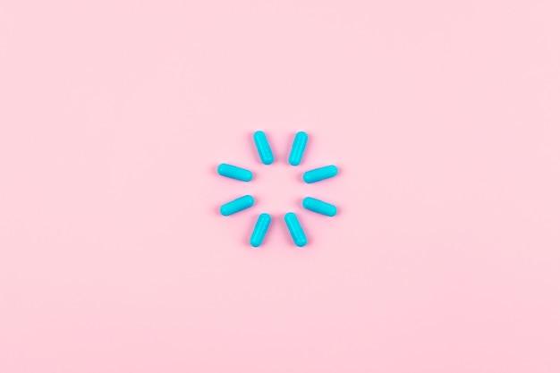 Pilules bleu vif en symbole de charge sur fond rose