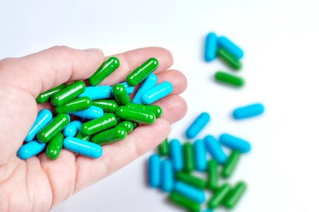 Pilules bleues et vertes dans la main agrandi.
