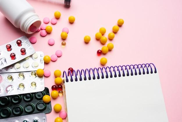 Pilules bloc-notes seringue fournitures médicales fond rose. photo de haute qualité