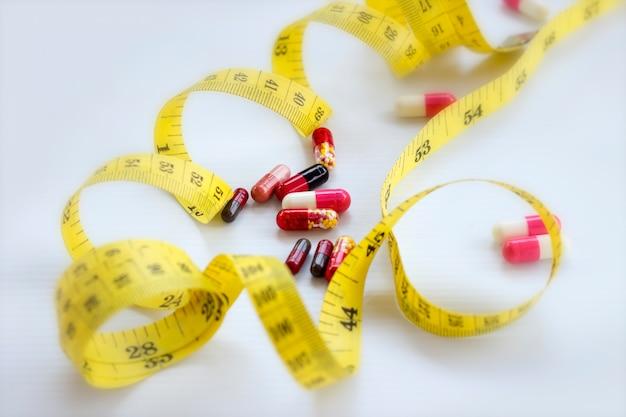 Pilules, capsule avec ruban à mesurer sur blanc