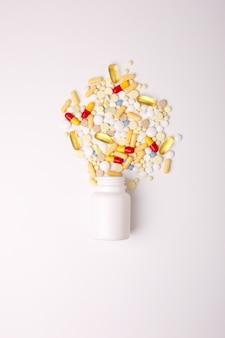 Pilules et capsules colorées débordant d'une vue de dessus de bouteille. comprimés médicaux, analgésiques, antibiotiques, vitamines et bocal en verre. magasin de pharmacie, clinique médicale, modèle de conception de bannière de pharmacie