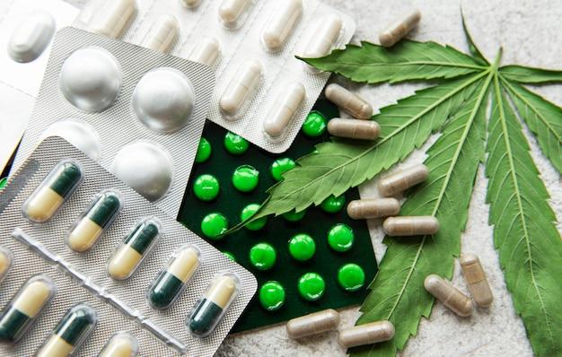 Pilules de cbd. groupe de capsules de cannabidiol cbd clair et feuille de chanvre sur fond de béton