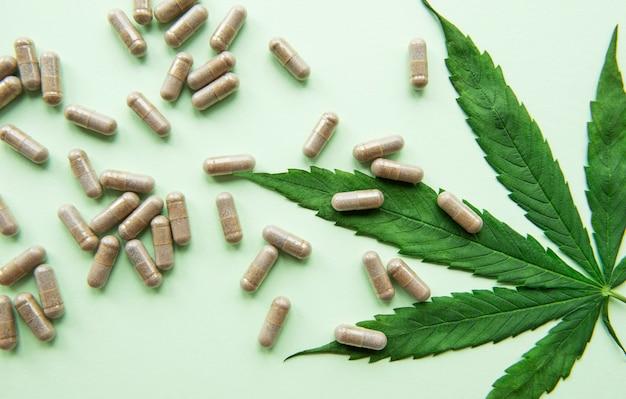 Pilules de cbd. groupe de capsules de cannabidiol cbd clair et feuille de chanvre sur fond vert