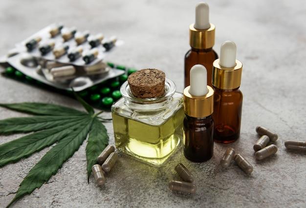 Pilules de cbd. groupe de capsules de cannabidiol cbd clair, d'huile et de feuille de chanvre sur fond de béton