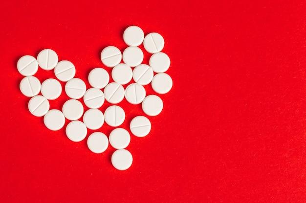 Pilules coeur en bouteille de pilules sur rouge, vue de dessus