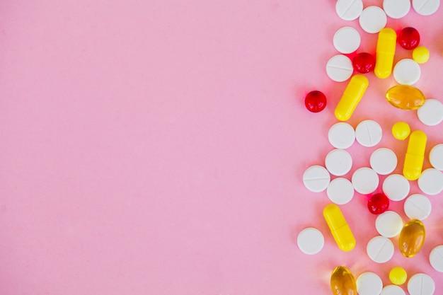 Pilules colorées et capsule sur rose.