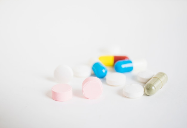 Pilules colorées et capsules sur fond blanc
