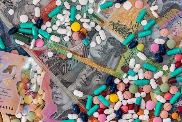 Pilules colorées dispersées sur des billets en dollars australiens