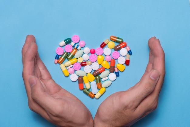 Pilules colorées en forme de coeur recouvertes de mains sur fond bleu.