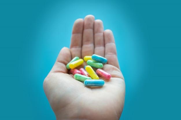 Pilules colorées et médicaments dans la main féminine