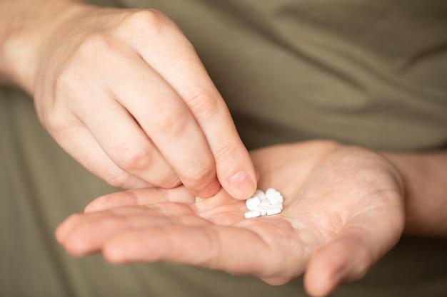 Pilules colorées et médicaments à la main