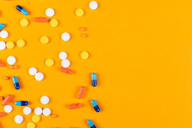 Pilules colorées sur une surface orange