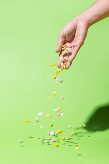 Pilules colorées tombant de la main sur fond vert.
