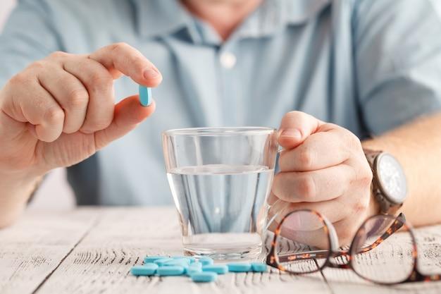 Des pilules colorées et un verre d'eau entre les mains des hommes. concept de santé