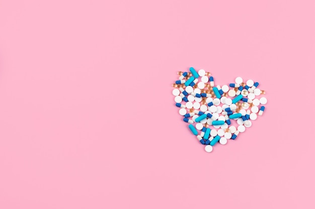 Pilules et comprimés bleus et blancs en forme de coeur