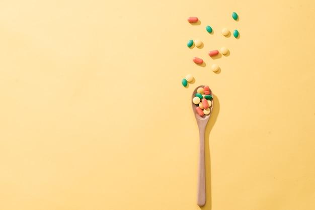 Pilules, comprimés et capsules de médecine pharmaceutique assortis sur la cuillère en bois