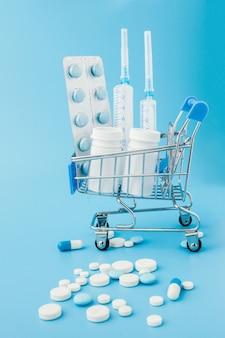 Pilules, comprimés et capsules de médecine pharmaceutique dispersés sur l'argent dollar isolé sur fond bleu. frais de médicaments.