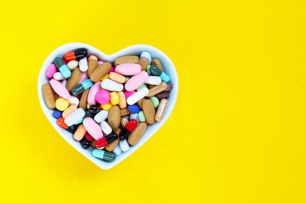 Pilules, comprimés et capsules de médicaments colorés dans un bol en forme de coeur