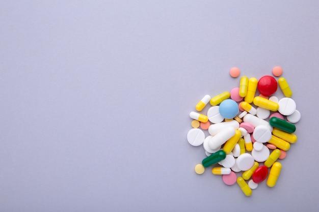 Pilules et comprimés colorés sur gris