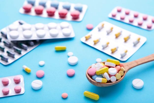 Pilules et comprimés colorés sous blister sur fond bleu, vue du dessus