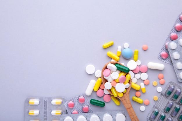 Pilules et comprimés colorés sous blister sur gris