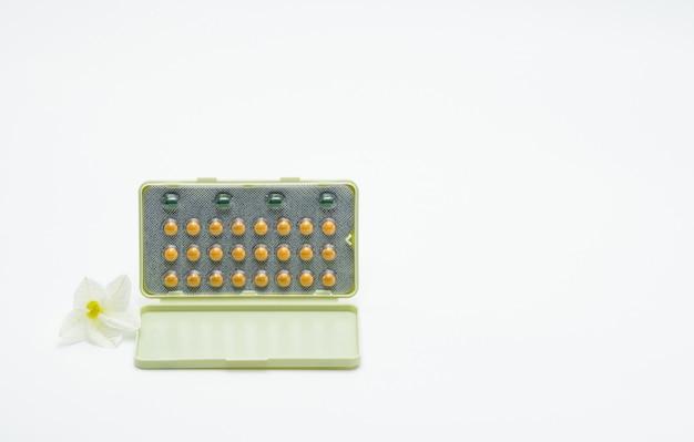 Pilules contraceptives ou pilule contraceptive avec étui en papier et fleur blanche sur fond blanc. concept de planification familiale. la thérapie de remplacement d'hormone. traitement de l'acné hormonal avec pilule anti-androgène.