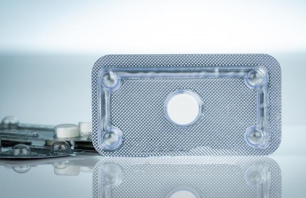 Pilules contraceptives d'urgence sous blister sur fond flou du matin après les pilules. cause médicamenteuse de la grossesse extra-utérine. contraception d'urgence pour éviter une grossesse après un rapport sexuel non protégé.